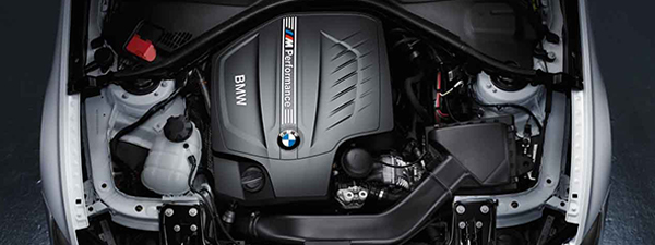 A close-up under the hood of a BMW focusing on an Original BMW Battery.