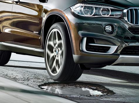 A close-up of the front of a brown BMW about to hit a large pothole on an asphalt road.