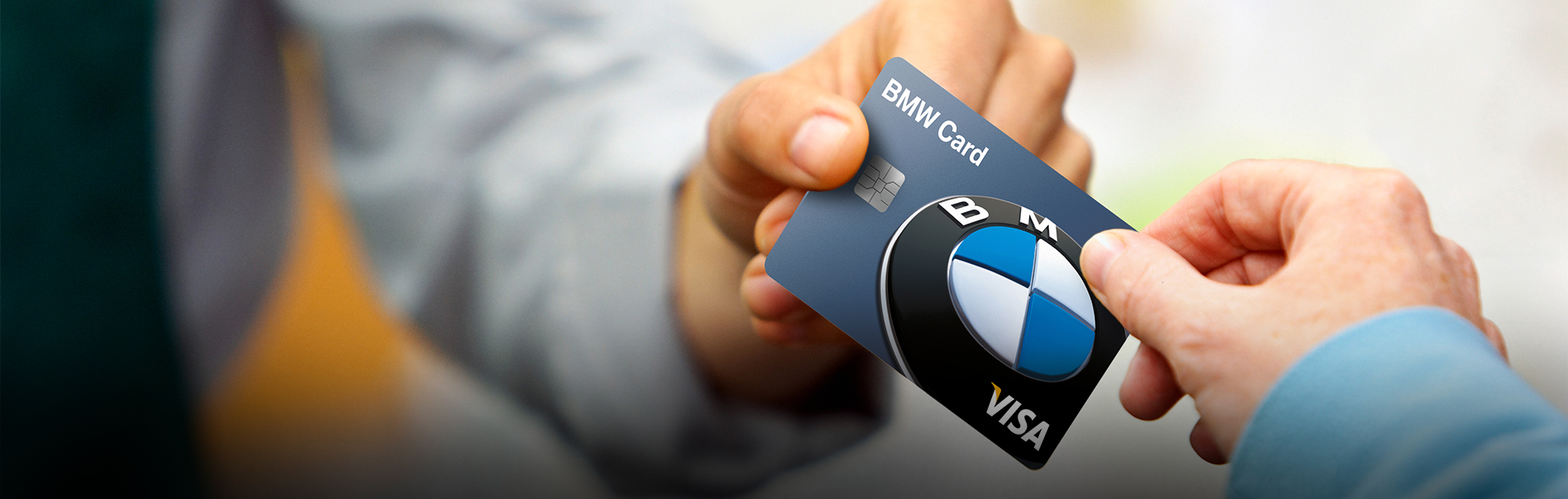 The BMW Family of Cards. Close-up of a Visa® BMW Credit Card being passed from a cashier in a green apron to the hand of a customer in a blue shirt.