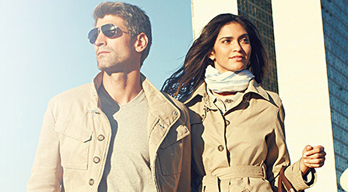 Original BMW Accessories. Up-angle view of a man and woman in matching beige BMW Collection Trench Coats walking together through an urban environment. The man wears sunglasses and the woman wears BMW scarf and carries a handbag, all from the BMW Lifestyle Collection.