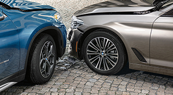 Side-view of a blue BMW X1 and silver BMW X5 in an accident situation.