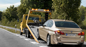 BMW Certified Collision Repair Centers. Rear view of a gold BMW sedan with rear bumper damage being loaded onto the flat bed of a tow truck.