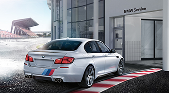 BMW FastService®. Rear view of a BMW M5 pulling off of a race track and into the entrance of a BMW Service Center.