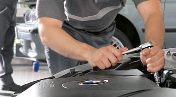 BMW Value Service. Close-up of a BMW Service Technician adjusting a bolt with a socket wrench under the hood of a BMW vehicle in a BMW Service Center.