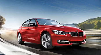 BMW Approved Tires. Motion-blurred three-quarter front view of a red BMW sedan driving on a highway on a sunny day.